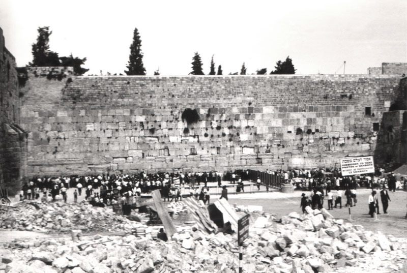 "Nella Magen Cassouto, 1967. The Wailing Wall. The plaza is already marked by various types of separation fences. The people who come to pray at the site are crowded against the Wall. From the center of the plaza, cleared of the demolition rubble that was the Maghrabia Quarter, a sign in three languages (Hebrew, English and French) warns: ""Photography forbidden on the Sabbath"". Perhaps out of consideration, the sign does not include the indigenous language of those who – until several days earlier – lived here. In the foreground, the rubble of the Maghrabia Quarter."