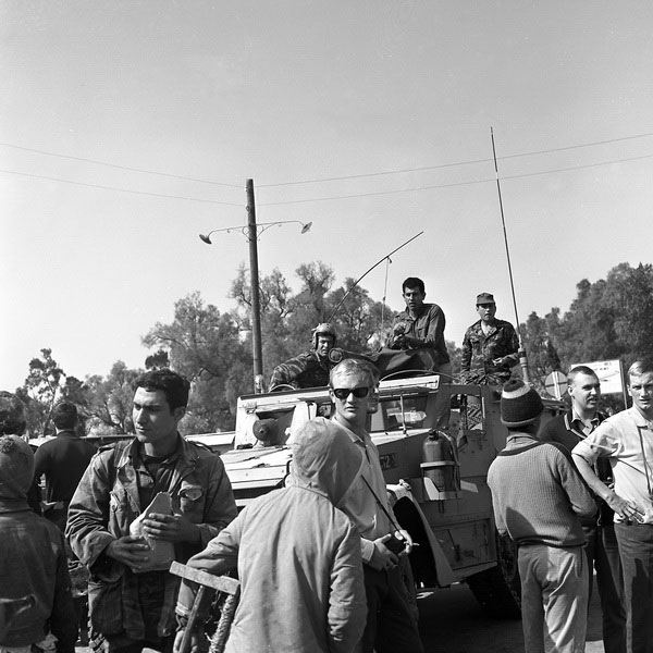 Ariela Shavid, 1968. Gaza. The soldiers and tourists look to the left, towards something going on outside the frame and hidden from its viewers. The only thing obvious to the viewer is the fact that the two Palestinian boys appearing in the frame turn their backs to that same occurrence and attempt to get away stealthily.  They do not seem interested or are not allowed to watch it. Is a mass arrest taking place there, or perhaps a forbidden political gathering?
