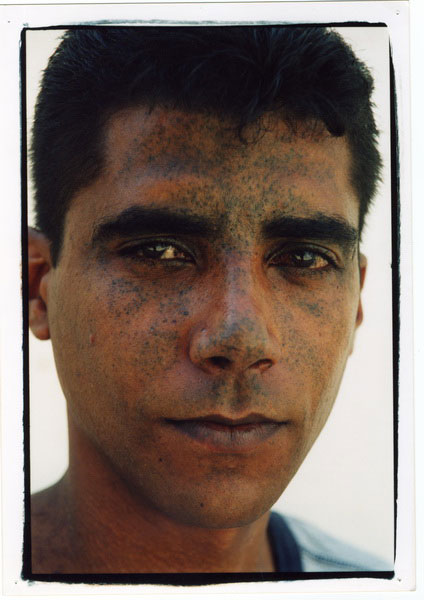 "Miki Kratsman	, 2001. Jenin. Until his portrait was taken, Zachariah Zbeide was wanted by the security services, but his face was unfamiliar. Courtesy of the photographer, and his own exposure to the camera, he passed over this game of hide-and-seek with the GSS – that had remained clandestine, turning him into a ""wanted"" security outlaw – into the public sphere in which he wishes to appear now through a direct portrait, identified and defiant, as a freedom fighter against the Occupation and the ""targeted executions"" apparatus it had created."