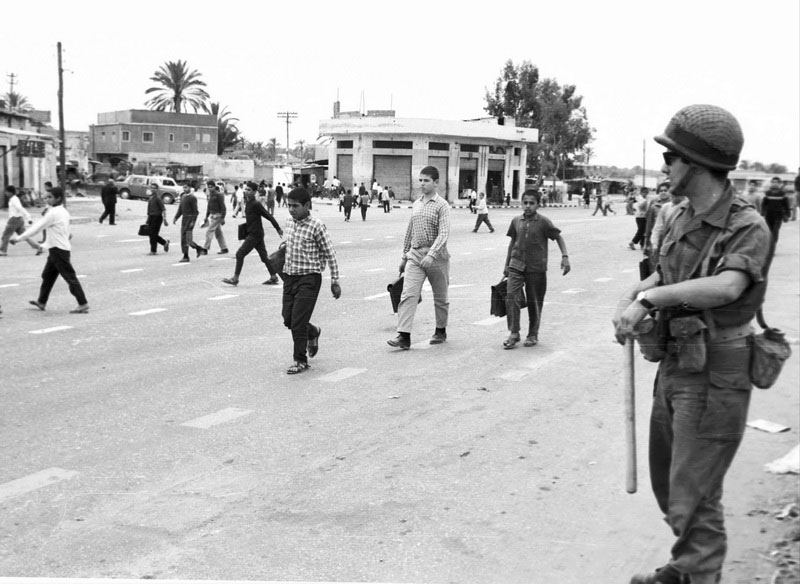 Avi Simchoni, 1969. Gaza. The distance kept among boys walking down the street with their schoolbags is not characteristic of children walking home from school. Their own experience and the presence of a soldier – a club in his right hand – are ample reminder to avoid walking in groups if they do not want to be suspected of political gathering.