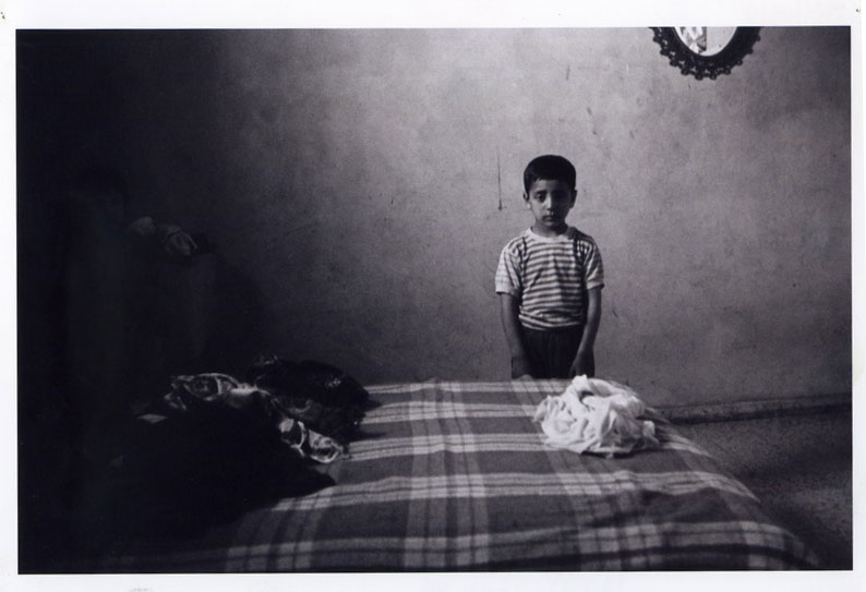 Oded Yedaya, 1989. Gaza. House searches in the middle of the night. The additional child on the left, absorbed in the dark, stands behind the bed, his hands lowered and his gaze to the camera. When the photographer facing them broke into their home in uniform in the middle of the night, did they have any other way of understanding his armed presence except as an order to stand still, braced and ready for the next command?